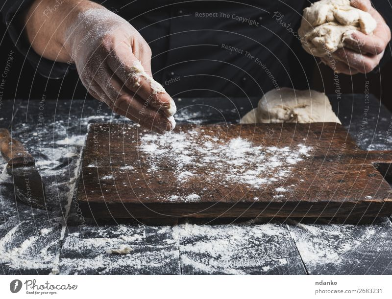 chef in black jacket kneads dough Dough Baked goods Bread Nutrition Skin Table Kitchen Cook Human being Man Adults Hand Wood Make Black White Tradition Baking
