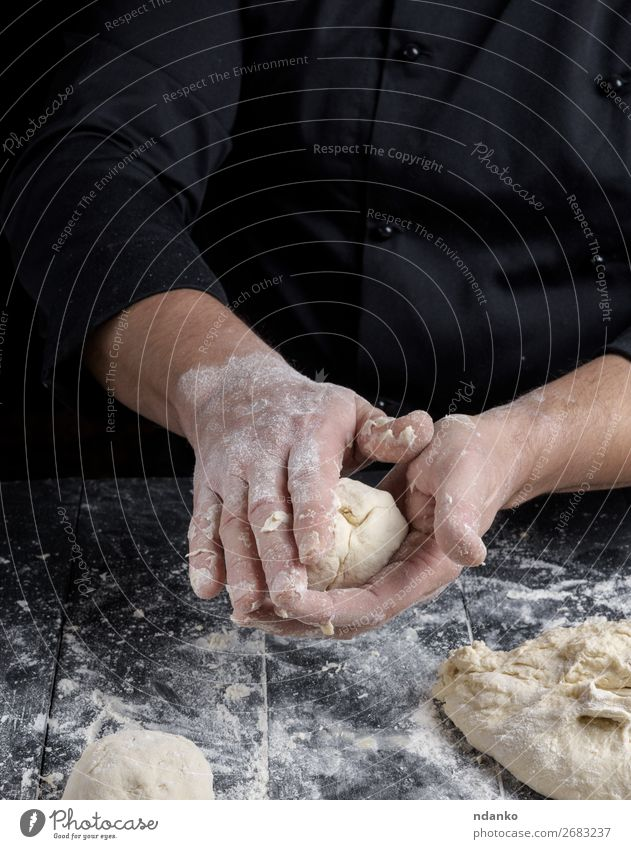 cook making dough balls on a black wooden table Human being Man White Hand Black Adults Wood Nutrition Table Skin Kitchen Baked goods Tradition Cooking Bread