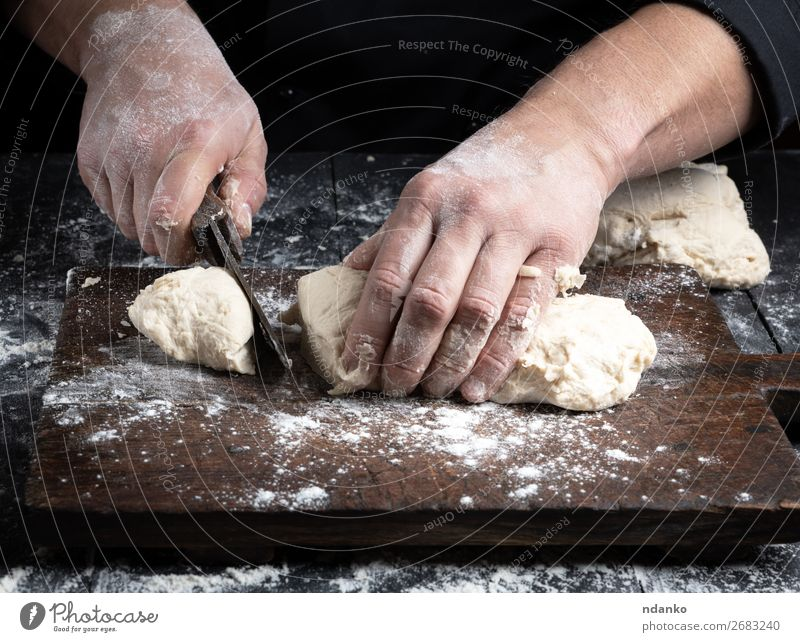 chef cuts white wheat flour dough into pieces Dough Baked goods Bread Nutrition Table Kitchen Cook Human being Man Adults Hand Wood Make Black White Tradition
