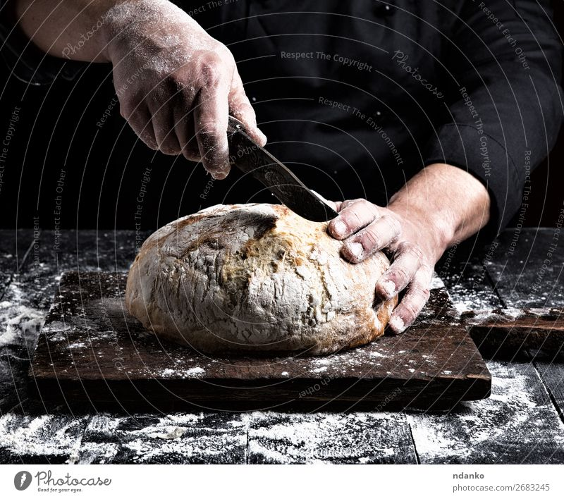 man cuts with a knife a round whole loaf Bread Nutrition Knives Table Kitchen Human being Hand Fingers Wood Make Dark Fresh Brown Black White Tradition Baking