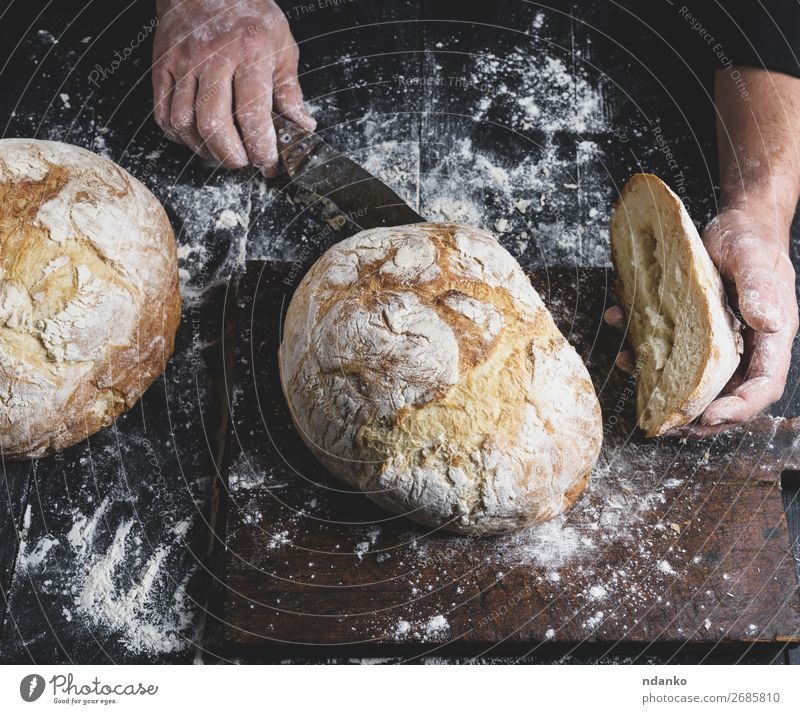 man cuts baked round bread on a brown wooden board Bread Nutrition Table Kitchen Human being Hand Fingers Wood Make Dark Fresh Brown Black White Tradition whole