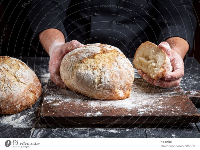 cook in a black tunic holds fresh baked bread Bread Nutrition Table Kitchen Human being Hand Fingers Wood Make Dark Fresh Brown Black White Tradition Baking