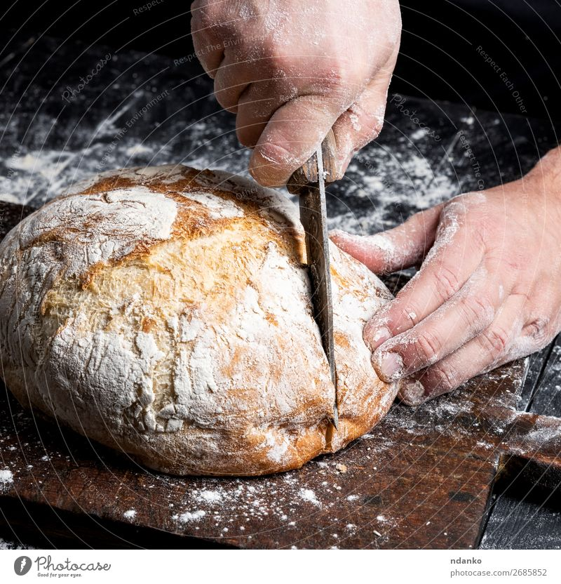 male hands cut a knife round baked bread Bread Nutrition Knives Table Kitchen Human being Hand Fingers Wood Make Dark Fresh Brown Black White Tradition Baking