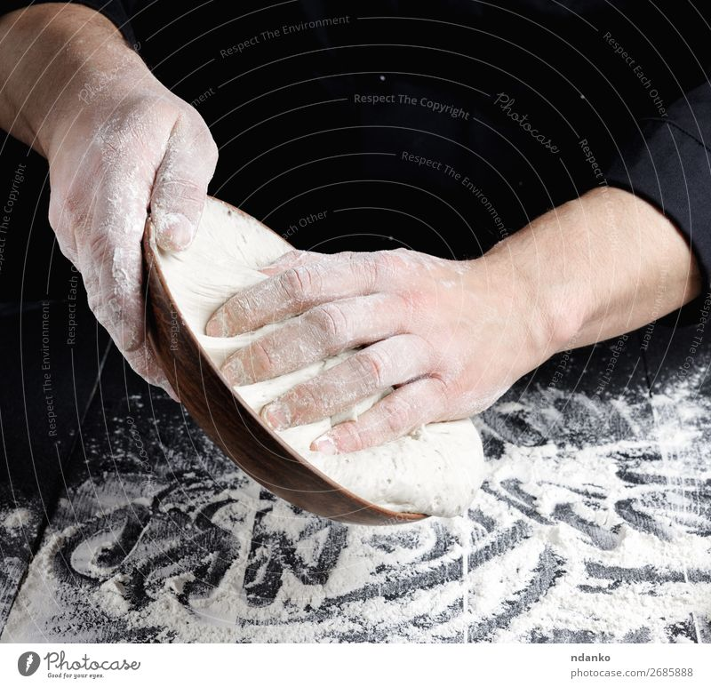 man's hands knead white wheat flour dough Dough Baked goods Bread Nutrition Plate Table Kitchen Cook Man Adults Hand Wood Make Fresh Black White Tradition