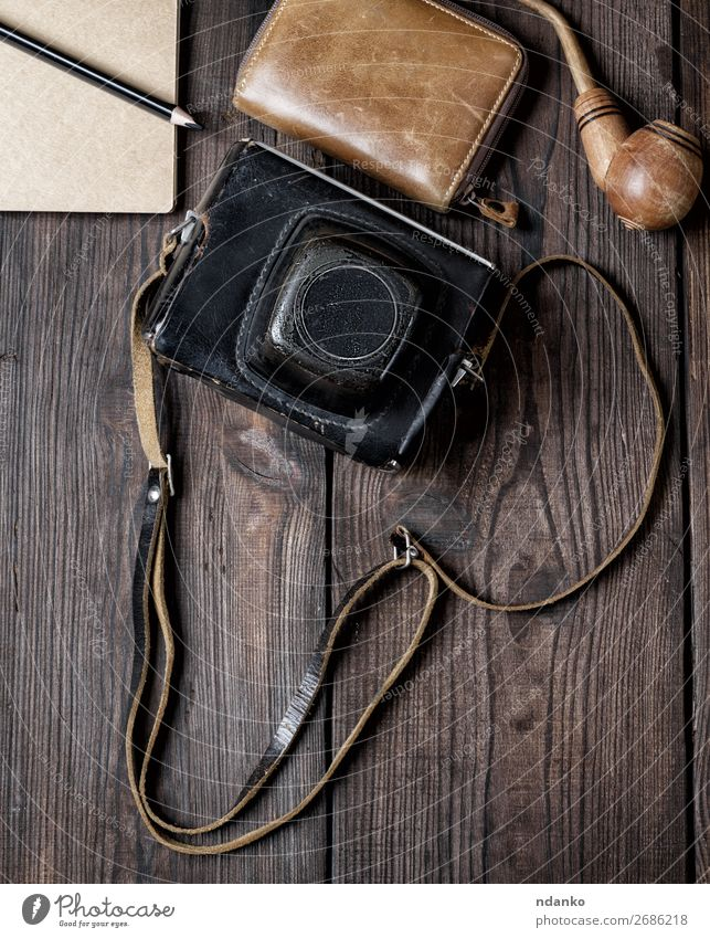 old vintage camera in a case on a wooden background Lifestyle Vacation & Travel Trip Camera Leather Accessory Wood Old Retro Brown Black Adventure casual