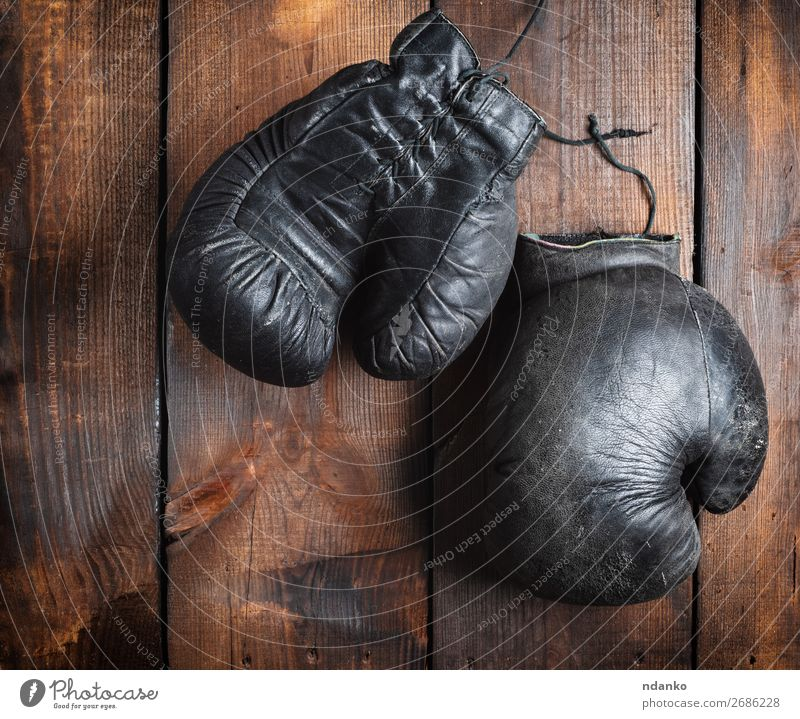 very old black boxing gloves Sports Leather Ring Gloves Wood Old Fitness Retro Brown Black Protection Competition Gymnasium Action Ancient Antique background