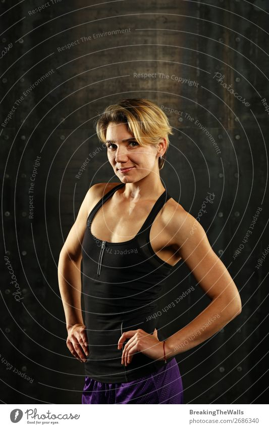 Close up front upper body portrait of one young athletic woman in sportswear in gym over dark background, looking at camera and smiling Lifestyle Sports Fitness