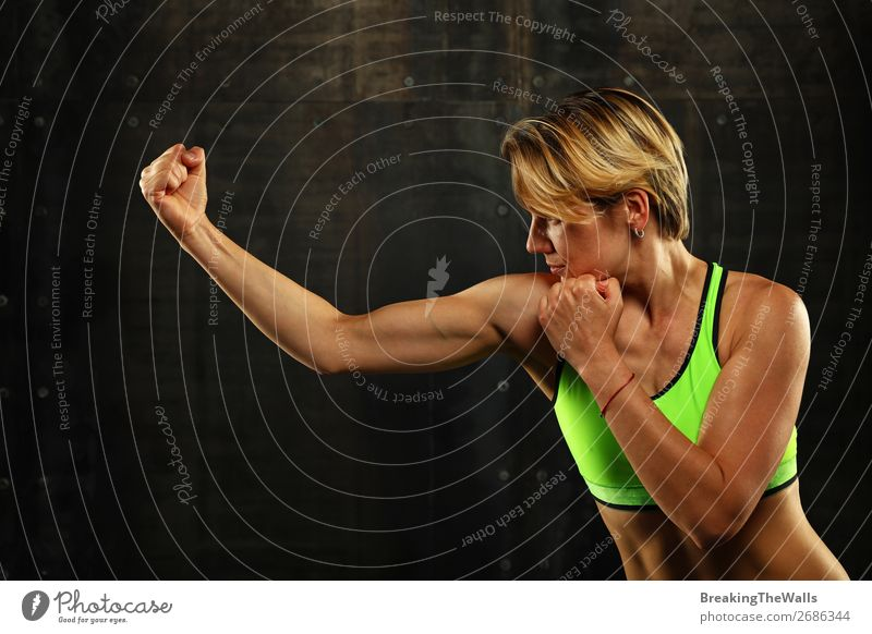Close up side view profile portrait of one young athletic woman shadow boxing in sportswear in gym over dark background, looking away Sports Martial arts