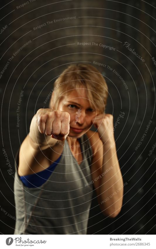 Close up front portrait of one young middle age athletic woman in sportswear in gym over dark background, standing in boxing stance with hands and fists, looking at camera
