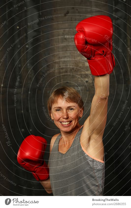 Front portrait of young adult woman in red boxing gloves with hand up gesture of winner or champion, smiling and looking at camera Joy Sports Fitness