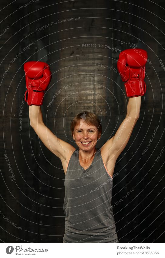 Front portrait of young adult woman in red boxing gloves with two hands up gesture of winner or champion, smiling and looking at camera Joy Sports Fitness