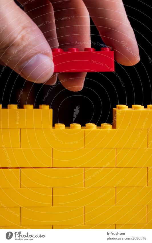 game bricks, yellow wall, red brick in hand Playing Model-making House building Redecorate Craftsperson Craft (trade) Construction site Fingers Toys Plastic