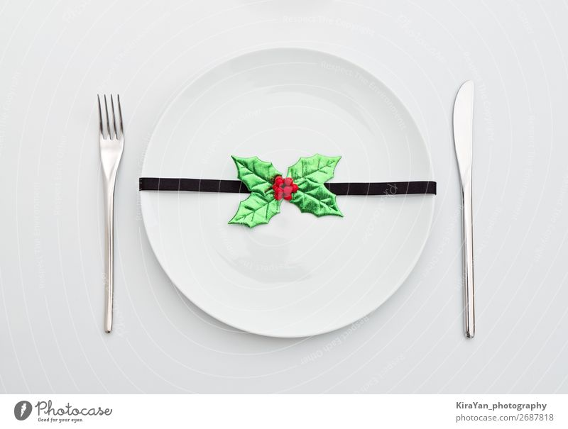 Christmas decoration with holly leaves on white plate Dinner Plate Cutlery Fork Decoration Restaurant Feasts & Celebrations Christmas & Advent New Year's Eve