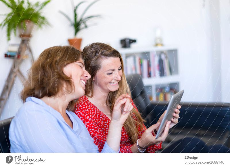 Women at home sitting on sofa while using a tablet PC Lifestyle Joy Happy Beautiful Relaxation Flat (apartment) House (Residential Structure) Sofa To talk