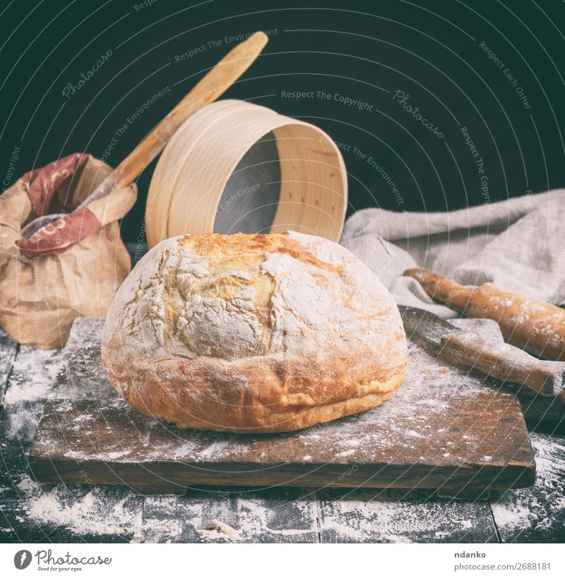 baked round white wheat bread Dough Baked goods Bread Knives Spoon Table Kitchen Sieve Wood Make Dark Fresh Brown Black White Tradition Baking Bakery board