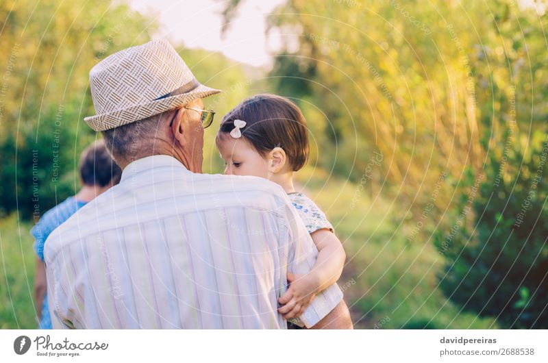 Back view of senior man holding baby girl in his arms Lifestyle Happy Relaxation Summer Child Human being Baby Toddler Woman Adults Man Parents Grandfather