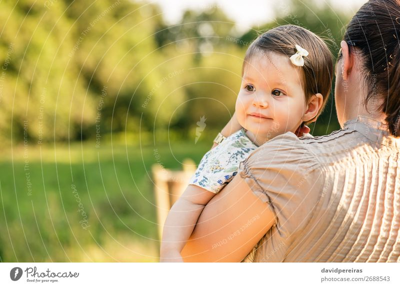 Back view of mother holding baby girl in her arms Lifestyle Joy Happy Beautiful Face Relaxation Summer Child Baby Toddler Woman Adults Parents Mother