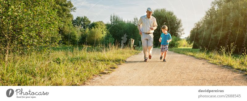 Senior man and happy child running outdoors Joy Happy Playing Child Human being Boy (child) Man Adults Grandfather Family & Relations Infancy Nature Tree Park