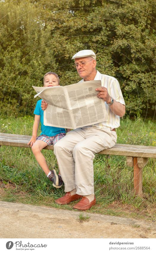Senior man and bored child reading newspaper outdoors Lifestyle Happy Relaxation Leisure and hobbies Reading Child School Human being Boy (child) Man Adults