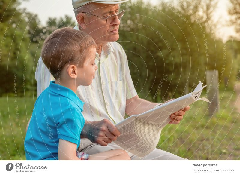 Senior man and child reading a newspaper outdoors Lifestyle Happy Relaxation Leisure and hobbies Reading Child School Human being Boy (child) Man Adults Parents