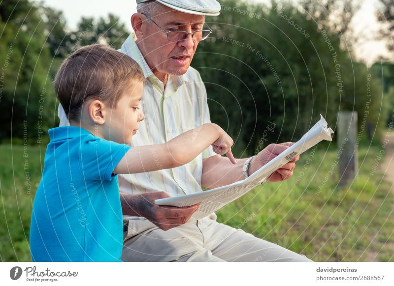 Senior man and child reading a newspaper outdoors Lifestyle Happy Leisure and hobbies Reading Child School Human being Boy (child) Man Adults Parents