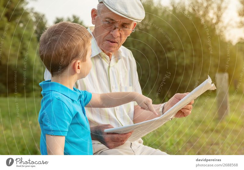 Senior man and child reading a newspaper outdoors Child Human being Nature Man Old Hand Lifestyle Adults Family & Relations Happy Boy (child) School Together