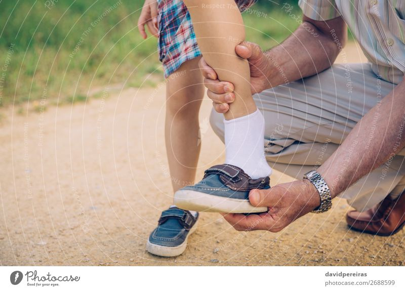 Grandfather putting shoe to his grandson outdoors Lifestyle Leisure and hobbies Summer Garden Child Human being Boy (child) Man Adults Parents