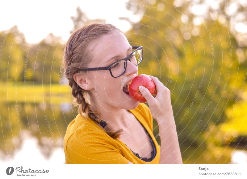 Young woman bites an apple Food Apple Eating Lifestyle Joy Healthy Healthy Eating Well-being Summer Feminine Youth (Young adults) 1 Human being 13 - 18 years