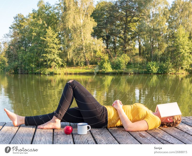 Woman with a book on her face lies by the lake Lifestyle Freedom Summer Sunbathing Human being Feminine Young woman Youth (Young adults) 1 18 - 30 years Adults