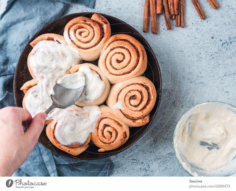 Hand Spreading Frosting on Cinnamon Rolls, copy space cinnamon rolls bun swedish womans hand spreading frosting skillet vegan kanelbullar pumpkin spice topping