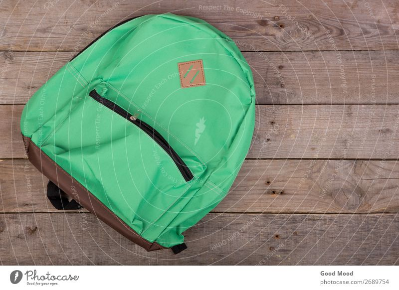 Green school backpack on brown wooden table Vacation & Travel Trip Table Child School Academic studies Tool Wood Brown Backpack bag background supplies