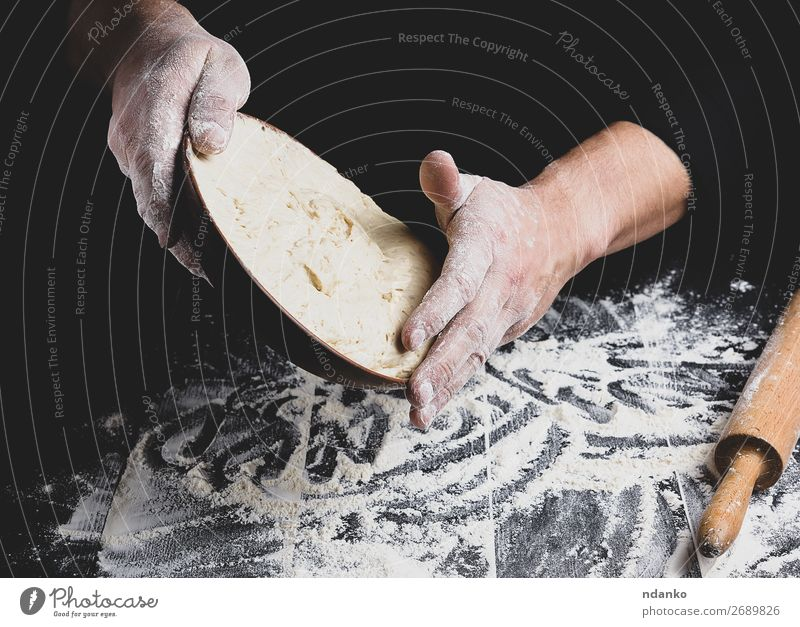 male hand holding a ceramic plate with yeast dough Dough Baked goods Bread Nutrition Plate Table Kitchen Cook Man Adults Hand Wood Make Fresh Black White