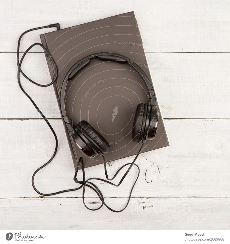 Audio book concept with black book and headphones Leisure and hobbies Playing Reading Music School Study Headset Technology Media Book Library Paper Wood