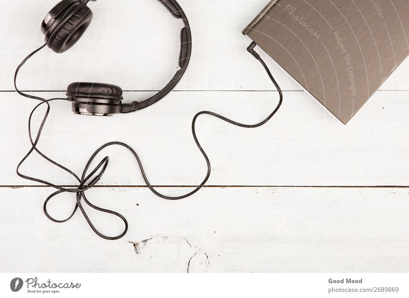 Audio book concept with black book and headphones Leisure and hobbies Reading Music Headset Technology Media Book Library Wood Listening Black White Idea School