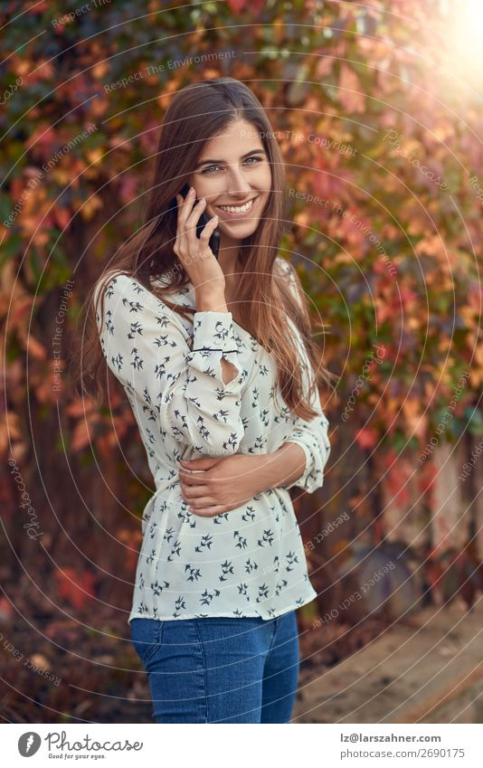 Smiling young woman chatting on a mobile in autumn Happy Face Summer Business Telephone PDA Woman Adults 1 Human being 18 - 30 years Youth (Young adults) Autumn