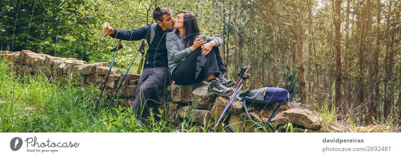 Couple kissing while making a break to do trekking Eating Drinking Lifestyle Leisure and hobbies Adventure Mountain Hiking Sports Climbing Mountaineering