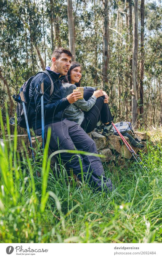 Couple pausing while doing trekking Woman Human being Nature Man Landscape Tree Forest Mountain Eating Lifestyle Adults Autumn Meadow Sports Happy Grass
