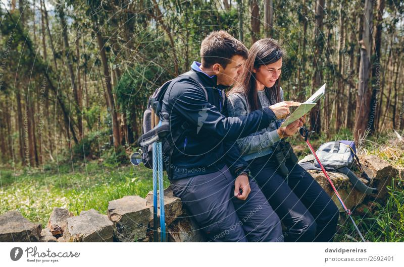 Couple doing trekking sitting looking at a map Leisure and hobbies Trip Adventure Sightseeing Mountain Hiking Sports Human being Woman Adults Man Nature
