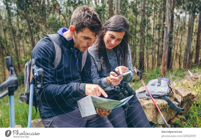 Couple doing trekking sitting looking mobile and map Trip Adventure Sightseeing Mountain Hiking Sports PDA Human being Woman Adults Man Nature Autumn Tree