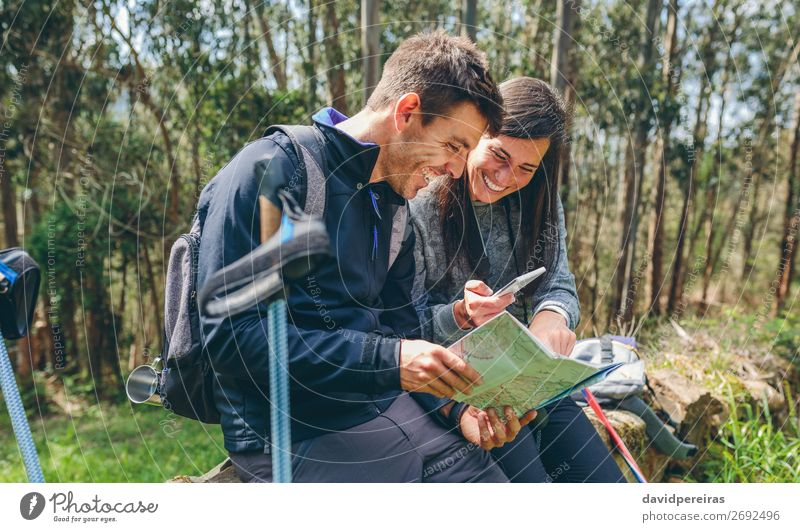 Couple doing trekking sitting looking mobile and map Joy Happy Trip Adventure Sightseeing Mountain Hiking Sports PDA Human being Woman Adults Man Nature Autumn