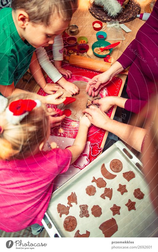 Baking Christmas cookies. Christmas gingerbread cookies in many shapes decorated with colorful frosting, sprinkle, icing, chocolate coating, toppers, put on table. Baking traditional cookies. Family celebrating Christmas. Baking at home. Baked sweet cookie