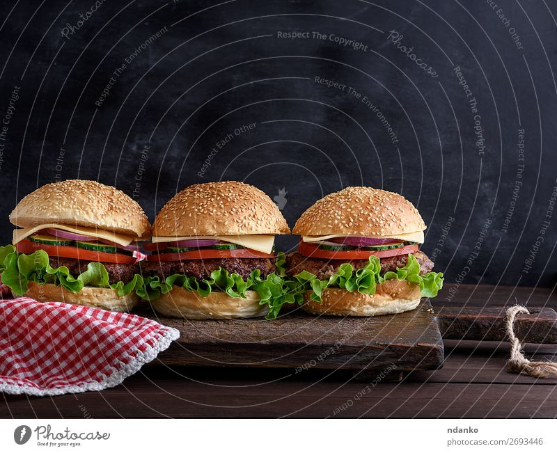 three hamburgers with vegetables Meat Cheese Vegetable Bread Roll Lunch Dinner Fast food Table Blackboard Wood Dark Fresh Red Salad American background bbq Beef