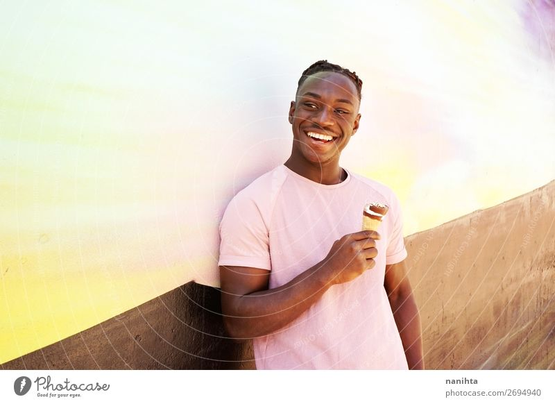 Young handsome black man holds an ice cream Human being Youth (Young adults) Man Summer Colour Young man Joy Black Healthy 18 - 30 years Food Eating Lifestyle