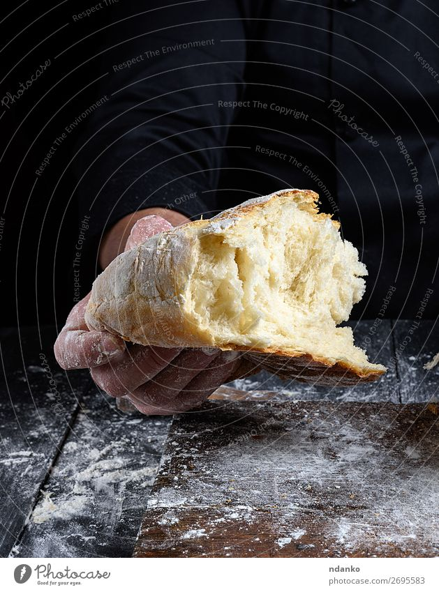 chef hand holds half baked white wheat flour bread Bread Nutrition Table Kitchen Human being Hand Fingers Wood Make Dark Fresh Brown Black White Tradition