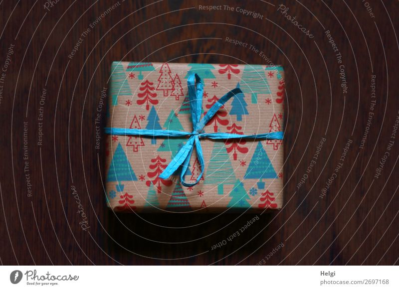 small parcel as a gift wrapped in red-blue-turquoise paper with Christmas motives and turquoise bast bow Piece of paper Packaging Decoration Bow Gift