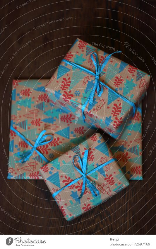 three wrapped gifts in christmassy patterned paper with blue bows lie on top of each other Feasts & Celebrations Christmas & Advent Birthday Packaging