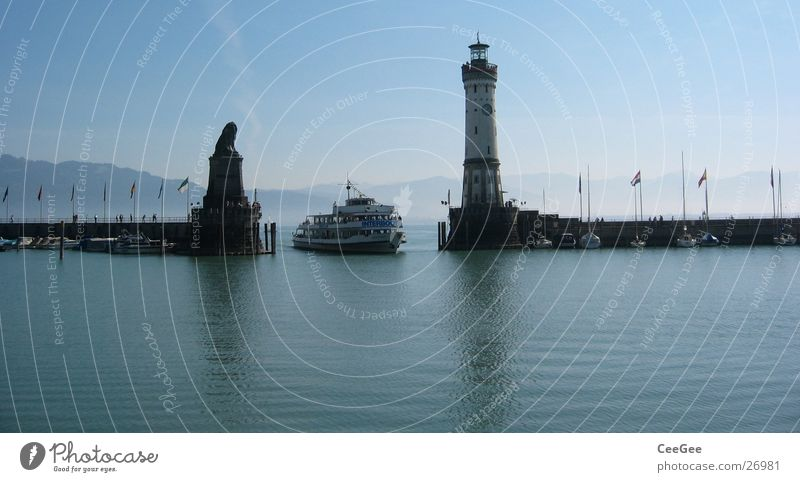 Lake Constance entrance Lindau Watercraft Lighthouse Lion Statue Wall (barrier) Jetty Reflection Driving Drop anchor Europe Germany Blue Harbour Island Mountain