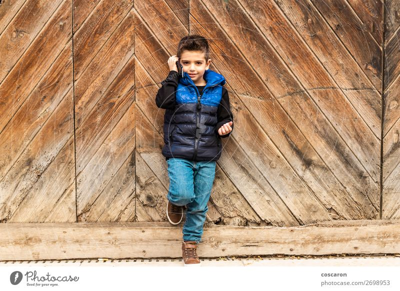 Little boy with a mibile phone with a wooden door background Lifestyle Style Design Beautiful Playing Vacation & Travel Winter House (Residential Structure)
