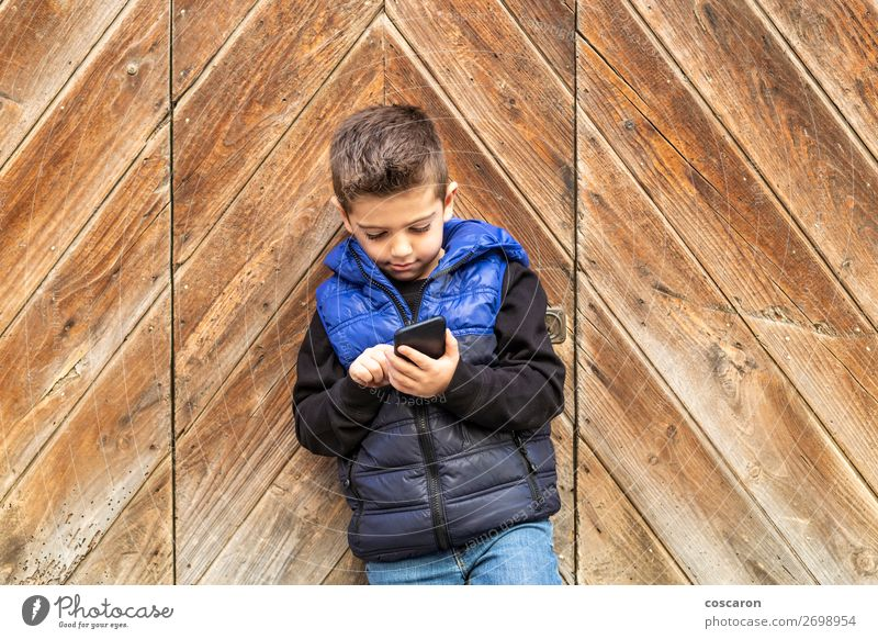Little boy with a mibile phone with a wooden door background Lifestyle Beautiful Playing Vacation & Travel House (Residential Structure) Child Telephone