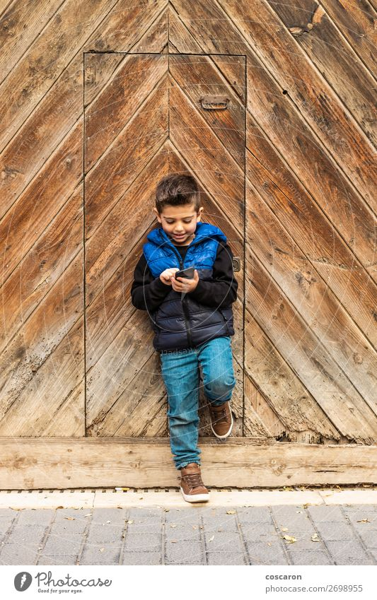 Little boy with a mibile phone with a wooden door background Child Human being Vacation & Travel Blue Town Beautiful House (Residential Structure) Joy Lifestyle